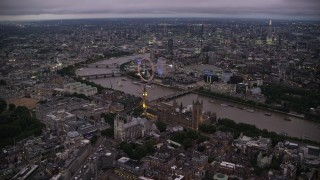 AX116_141 - 6K stock footage aerial video fly toward Big Ben, British Parliament, London Eye, and Westminster Abbey, London, England, night