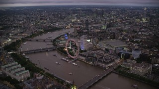 AX116_143 - 6K stock footage aerial video of flying over Big Ben toward London Eye and River Thames, London, England, night