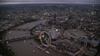 AX116_144 - 6K stock footage aerial video of approaching London Eye by the River Thames, London, England, night