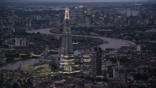 AX116_146 - 6K stock footage aerial video of flying by The Shard skyscraper by River Thames, London, England, night