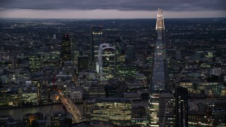 AX116_153 - 6K stock footage aerial video of flying by The Shard, Central London skyscrapers across River Thames, England, night