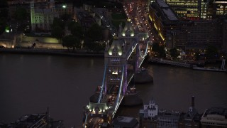AX116_156 - 6K stock footage aerial video of an orbit of Tower Bridge spanning River Thames, London, England, night