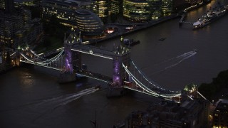 AX116_160 - 6K stock footage aerial video of flying by Tower Bridge spanning River Thames in London, England, night