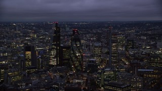 AX116_161 - 6K stock footage aerial video flyby Leadenhall Building, The Gherkin, Heron Tower in London, England, night