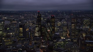 AX116_162 - 6K stock footage aerial video of Leadenhall Building, Gherkin, Tower 42, Heron Tower skyscrapers, London, England, night