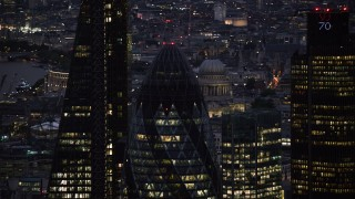 AX116_163 - 6K stock footage aerial video of orbiting the top of The Gherkin skyscraper in London, England, night