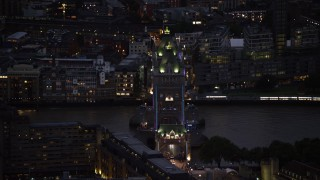 AX116_164 - 6K stock footage aerial video of passing the famous Tower Bridge over River Thames, London, England, night