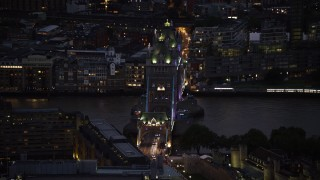 AX116_165 - 6K stock footage aerial video of slowly flying by Tower Bridge and River Thames, London, England, night