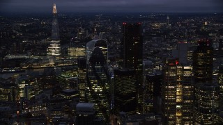AX116_167 - 6K stock footage aerial video of The Gherkin seen from Heron Tower, The Shard in background, London, England, night