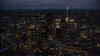 AX116_170 - 6K stock footage aerial video of passing by Central London skyscrapers, The Shard in background, England, night