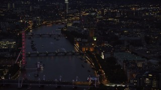 AX116_178 - 6K stock footage aerial video passing by London Eye, Big Ben and Parliament, and River Thames bridges, London, England, night