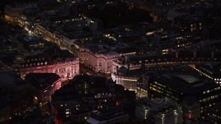 AX116_180 - 6K stock footage aerial video of flying by the bright lights of Piccadilly Circus, London, England, night