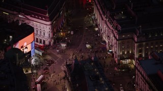 AX116_183 - 6K stock footage aerial video of orbiting crowds and double decker buses at Piccadilly Circus, London, England, night