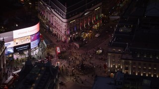AX116_184 - 6K stock footage aerial video orbit crowds and double decker buses at Piccadilly Circus, London, England, night