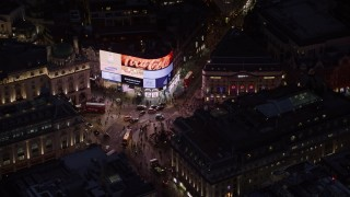 AX116_185 - 6K stock footage aerial video of orbiting crowds and buses at Piccadilly Circus, London, England, night