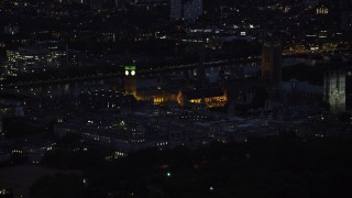 AX116_189 - 6K stock footage aerial video of flying by Big Ben, British Parliament and Westminster Abbey, London, England, night