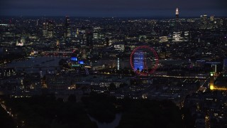 AX116_193 - 6K stock footage aerial video of passing cityscape, London Eye and Big Ben by River Thames, London, England, night