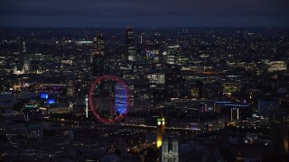 AX116_195 - 6K stock footage aerial video of the London Eye, Big Ben and distant skyscrapers, London, England, night