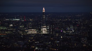 AX116_198 - 6K stock footage aerial video of The Shard towering over city buildings, London, England, night