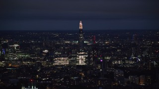AX116_199 - 6K stock footage aerial video of a view of The Shard towering over city buildings, London, England, night