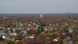 AX117_001 - 6K stock footage aerial video of suburban residential neighborhood in Autumn, Farmingdale, New York