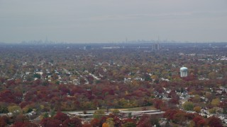 AX117_003 - 6K stock footage aerial video of a suburban neighborhood and NYC skyline in Autumn, Farmingdale, New York