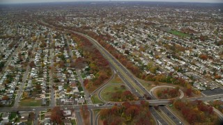 AX117_008 - 6K stock footage aerial video of suburbs and freeway with light traffic in Autumn, Massapequa, New York