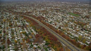 AX117_009 - 6K stock footage aerial video flyby suburbs and freeway with light traffic in Autumn, Massapequa, New York