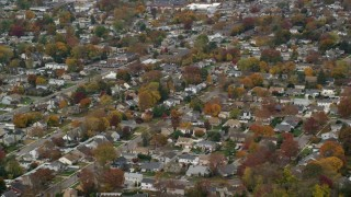 AX117_017 - 6K stock footage aerial video of suburban neighborhood in Autumn, North Bellmore, New York