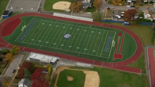 AX117_025 - 6K stock footage aerial video of a high school track and football field in Autumn, Merrick, New York