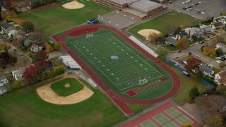 AX117_026 - 6K stock footage aerial video orbit high school track and football field in Autumn, Merrick, New York