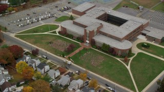 AX117_036 - 6K stock footage aerial video of flags on display at high school in Autumn, Merrick, New York