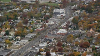 AX117_041 - 6K stock footage aerial video of homes and shops on a Main Street in Autumn, Bellmore, New York