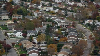 AX117_045 - 6K stock footage aerial video of passing suburban homes in Autumn, Bellmore, New York