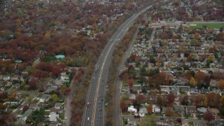 AX117_051 - 6K stock footage aerial video of light traffic on freeway by suburbs in Autumn, Seaford, New York