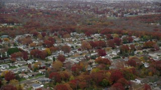 AX117_055 - 6K stock footage aerial video fly over suburbs toward nature preserve trees in Autumn, Massapequa, New York