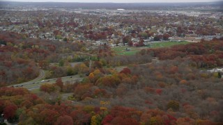 AX117_056 - 6K stock footage aerial video fly over suburbs and trees toward high school in Autumn, Farmingdale, New York