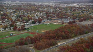 AX117_057 - 6K stock footage aerial video approach a high school in Autumn, Farmingdale, New York