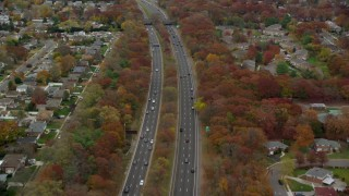 AX117_058 - 6K stock footage aerial video of a freeway with light traffic in Autumn, Farmingdale, New York