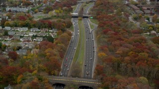 AX117_059 - 6K stock footage aerial video follow a freeway with light traffic in Autumn, Farmingdale, New York