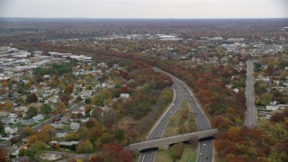AX117_060 - 6K stock footage aerial video tilt from freeway with light traffic to suburbs in Autumn, Farmingdale, New York