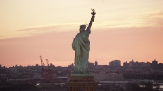 AX118_042 - 6K stock footage aerial video orbit back of the Statue of Liberty at sunrise, New York