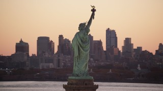 AX118_043 - 6K stock footage aerial video of orbiting the back of the Statue of Liberty at sunrise, New York