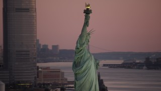 AX118_046 - 6K stock footage aerial video orbit Statue of Liberty at sunrise, with New York City in the background