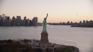 AX118_057 - 6K stock footage aerial video of circling around the side of the Statue of Liberty at sunrise, New York