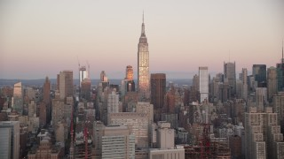 AX118_063 - 6K stock footage aerial video of the famous Empire State Building at sunrise in Midtown Manhattan, New York City