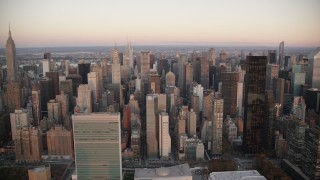 AX118_068 - 6K stock footage aerial video of the UN, Chrysler Building and skyscrapers at sunrise in Midtown, New York City