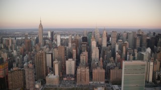 AX118_069 - 6K stock footage aerial video flyby the UN, Chrysler and Empire State Building at sunrise in Midtown, New York City