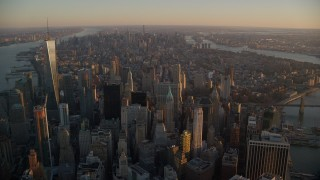 AX118_087E - 5.5K stock footage aerial video of Lower and Midtown Manhattan skyscrapers at sunrise, New York City