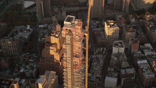 AX118_093 - 6K stock footage aerial video of an orbit of the 56 Leonard Street condo complex at sunrise in Tribeca, New York City